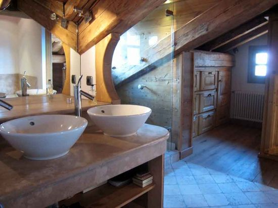 A bathroom with exposed roof beams.